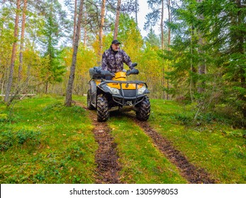 ATV. A man rides through the forest on an all-terrain vehicle. Quad bike. In the woods. Trip to the forest on ATV.