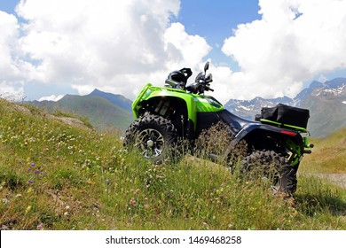 With the ATV in the mountains. A green ATV stands on a steep mountain path.