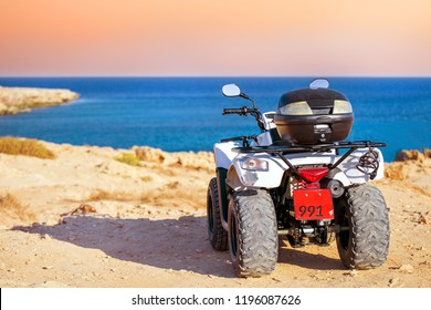ATV on the background of the shore sea on sunset. Travel trip on ATV concept. Rent ATV.