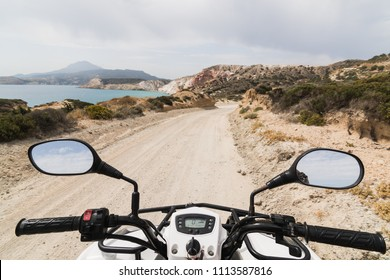 ATV quad bike driving along the coastal road along Aegean sea on Milos island, Greece. View from driver's seat.