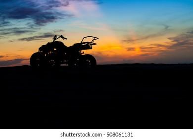 ATV quad biking in desert with colorful twilight dramatic sky, Muine sand dunes, Vietnam