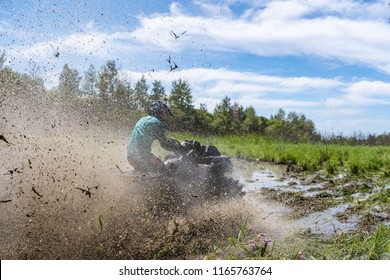 ATV Quad polaris rides fast on big dirt and makes splashes of dirty water