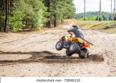 An ATV quadbike driver drifts and stunts on a sand rough terrain near forest, turns on a two wheels in a moment before accident.