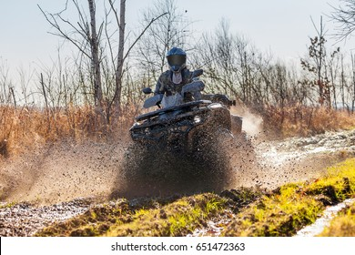 ATV racer drives through mud and water on a forest road