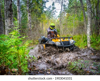 ATV racer in mud. He drives off-road in forest. ATV racer in taiga. Motocross in summer taiga. Extreme quad cycle riding. Ride through green forest on quad cycle. Motocross on a quad cycle