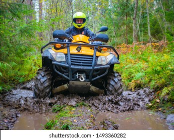 ATV racing. A man on a yellow quadrocycle. ATV tires in the mud. Man in a yellow helmet on a quad bike. A human came to the forest on an quadrocycle. ATV with a driver close-up. Extreme quad bike ride