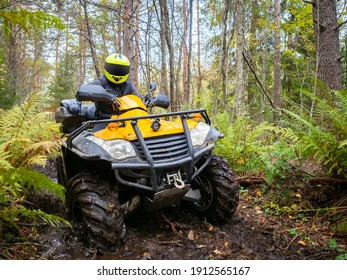 ATV racing in the woods. Extreme ATV racing off-road. Biker's journey in woods. Biker on a yellow ATV. Portrait of a biker in mud. Motocross in the green taiga. Participation in motocross