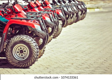 ATV red are parked in a row on road.