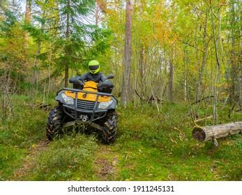 ATV-Fahrer während des Motocross. ATV fährt durch den Wald. Mann auf einem gelben Quad-Zyklus. ATV-Fahrer in Taiga. Er nimmt an einem Offroad-Rennen teil. Motocross im Wald. Extremsport auf dem Rad