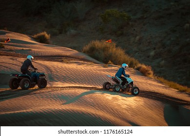 ATV Riders On The Sand Dunes At Sunset