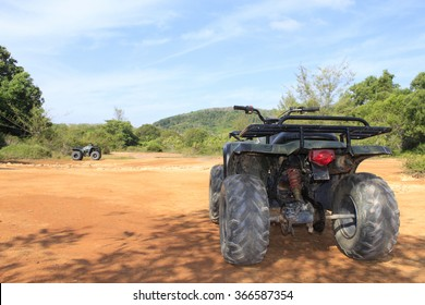 ATV stands on the ground in rubber tree field