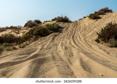 ATV tire tracks up sand dune hill