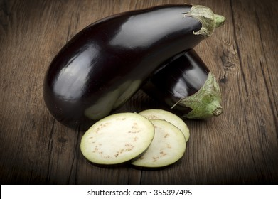 Aubergines eggplants and slices on wood background
