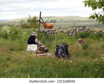 Aubrac, France - June 15, 2016: Elderly pilgrims resting on green grass, hiking stick in foreground. Picturesque Way of St James (Saint-Jacques). Pilgrimage route to Santiago de Compostela (Spain)