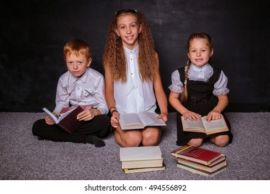Auburn boy and his two sisters sitting on the floor with books and reading. Black background. School concept