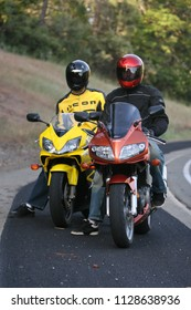 Auburn, CA - July 15, 2009: two motorcycle riders on the side of the road. Suzuki and Honda sports bikes.