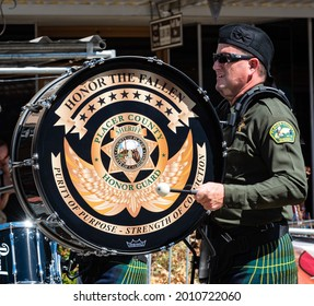 AUBURN, CA, U.;S.A. - JULY 4, 2021: Photo of a kilted Placer County Sheriff Honor Guard drummer playing a bass drum that says Honor the Fallen during the town's annual July 4 parade.