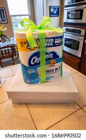 AUBURN, CA/U.S.A. - MARCH 28, 2020: Photo of a pack of Charmin toilet paper wrapped with a bright green ribbon on top of two wrapped gifts boxes in a kitchen. The items are gifts for family members.