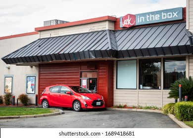 AUBURN, CA/U.S.A. - MARCH 31, 2020: Photo of a red car pulling up to pick up a food order at a Jack-in-the-Box. The restaurant is only open for drive through because of COVID19.