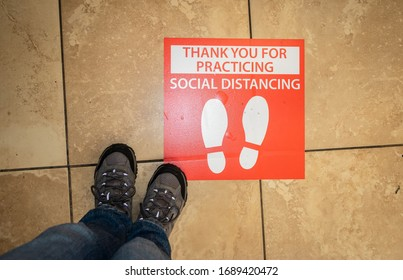 AUBURN, CA/U.S.A. - MARCH 31, 2020: Photo of a pair of hiking shoes next to a red sign with footprints telling people where to stand in a supermarket line because of social distancing.