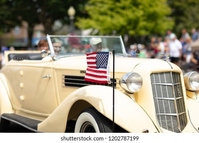 Auburn, Indiana, USA - September 9, 2018 The Auburn Cord Duesenberg Festival, An Auburn classic car carrying an american flag driving down the street during the parade