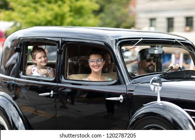 Auburn, Indiana, USA - September 9, 2018 The Auburn Cord Duesenberg Festival, a family driving in An Auburn classic car driving down the street during the parade