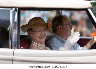 Auburn, Indiana, USA - September 9, 2018 The Auburn Cord Duesenberg Festival, man and women wearing retro clothing driving An Auburn classic car driving down the street during the parade
