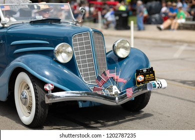 Auburn, Indiana, USA - September 9, 2018 The Auburn Cord Duesenberg Festival, An Auburn classic car with american flags on the front bumper driving down the street during the parade