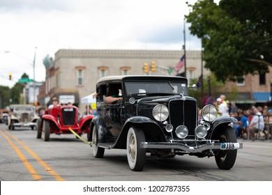 Auburn, Indiana, USA - September 9, 2018 The Auburn Cord Duesenberg Festival, An Auburn classic car towing another auburn driving down the street during the parade