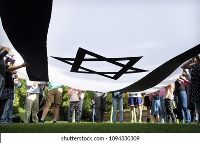 AUCKLAND - APR 22 2018:Israeli Jewish people holding a giant national flag of Israel on Israels 70's independent day,  commemorating the Israeli Declaration of Independence on 14 May 1948.