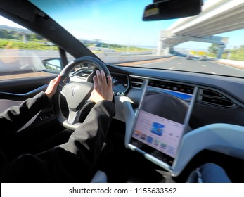AUCKLAND - AUG 12 2018:Person driving a Tesla plug-in electric car Model X, a luxury, crossover utility vehicle (CUV) , on a motorway. in 2016 seventh among the world's best-selling plug-in cars.
