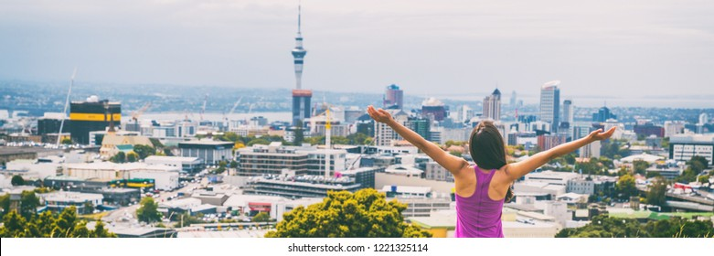Auckland city happy woman in New Zealand banner. Skyline view from Mount Eden of Sky tower, arms up in freedom and happiness at top of Mt Eden urban park famous tourist attraction.