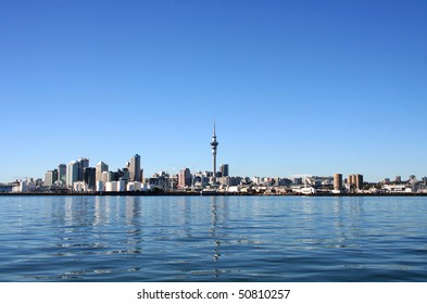 Auckland City and Sky Tower, New Zealand with bright blue clear skies viewed from across the harbour