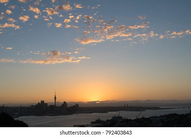 Auckland city sunset with the sun setting behind the Waitakere ranges with the Sky Tower in frame. Spotty yellow clouds in the sky. Taken from Devonport Hills