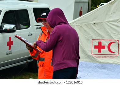 AUCKLAND - DEC 7:Red cross volunteer assist a victim when a rare tornado ripped through Hobsonville in Auckland, NZ on December 7, 2012.It killed 3 and 250 people were left homeless and without power.