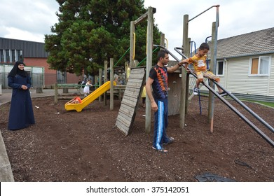AUCKLAND - FEB 21 2016:A Syrian refugee family play together on a playground at the Mangere Refugee Resettlement Centre.New Zealand annual intake is 750 refugee fleeing war in Syria.