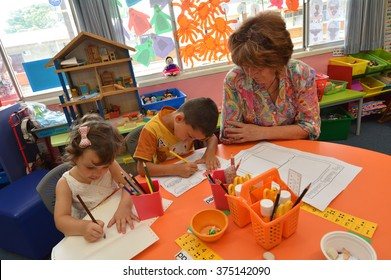 AUCKLAND - FEB 21 2016:A teacher interacts with Syrian children at the Mangere Refugee Resettlement Centre. New Zealand annual intake is 750 refugee fleeing war in Syria.