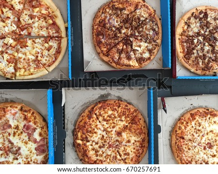 AUCKLAND - JULY 01 2017: Selection of Domino's Pizza on a table. Founded in 1960, Domino's is the second-largest franchised pizza chain in the United States after Pizza Hut in 81 countries.