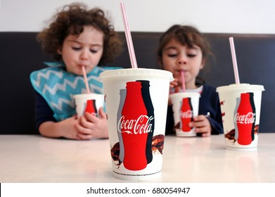 AUCKLAND - JULY 18 2017:Two young girls (Talya and Naomi Ben-Ari age 07- 03) drinking Coca Cola. Sugary drinks are a major contributor to health conditions such as obesity, diabetes and tooth decay.