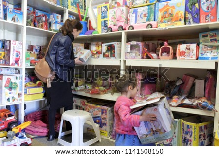 AUCKLAND - JULY 24 2018:Mother and child selecting toys in toy library.Toy libraries offer wide range of toys appropriate for children at different development stages without  family need to buy them.