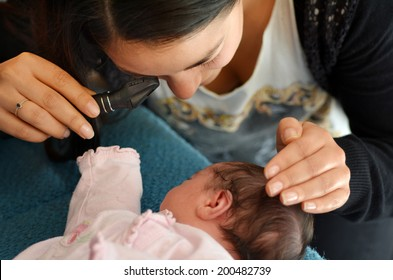 AUCKLAND - JUNE 14 2014:Midwife checks newborn baby red reflex examination.The test detect conditions that distort or suppress the normal visual image and can lead to blindness in children.