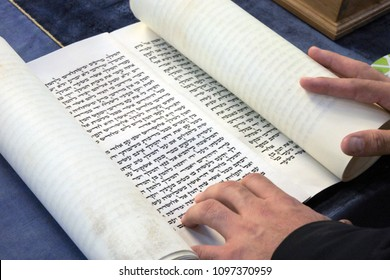 AUCKLAND - MAR 01 2018:Jewish Rabbi reads The Megillah Scroll (Book of Esther) on Purim Jewish holiday.It is one of the only books in the Hebrew Bible that do not explicitly mention God.