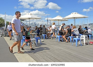 AUCKLAND - MAR 25 2018:Visitors dinning in Westhaven Marina against Auckland skyline.In 2012 readers of UK paper The Telegraph voted New Zealand the best country in the world to go to on holiday.