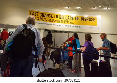 AUCKLAND - MAY 21 2015:Passengers under Biosecurity sign in Auckland Airport.New Zealand has very strict biosecurity procedures at airports and ports to prevent the introduction of pests and diseases.