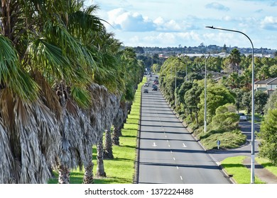Auckland / New Zealand - April 8 2019: Aerial view of Te Irirangi Drive two lane avenue with palm trees and traffic