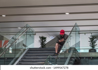 Auckland / New Zealand - August 9 2019: View of man with red cap sitting on stairs and holding mobile phone