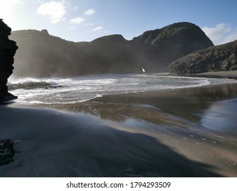 Auckland / New Zealand - August 9 2020: View of Piha Gap and tidal lagoon with Camel Rock island in background