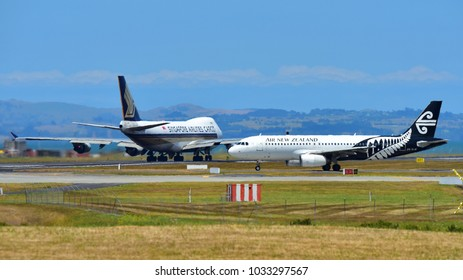 AUCKLAND, NEW ZEALAND - DECEMBER 17: Air New Zealand Airbus A320 taxiing while Singapore Airlines Boeing 747-400 freighter takes off at Auckland International Airport on December 17, 2017 in Auckland