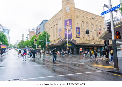 AUCKLAND NEW ZEALAND - DECEMBER 23; People cross Queen Street and Wellesley Street intersection in front of historic Civic Theater on wet day December 23 2018 Auckland New Zealand