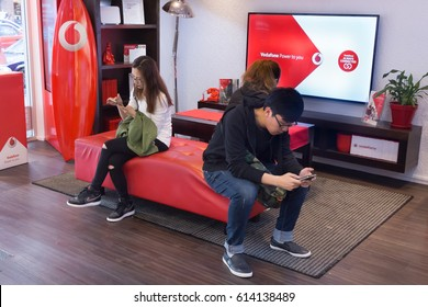 Auckland, New Zealand - February 17, 2017: Asian costumers using their mobile inside a Vodafone store in Auckland.